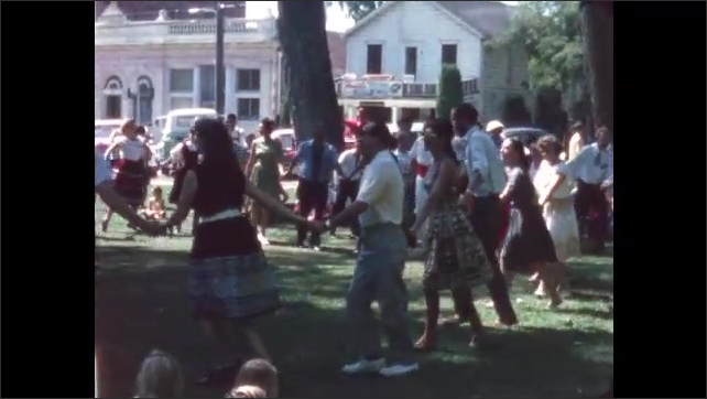 1960s: People in a park hold hands and dance together in a circle. Couples dance.