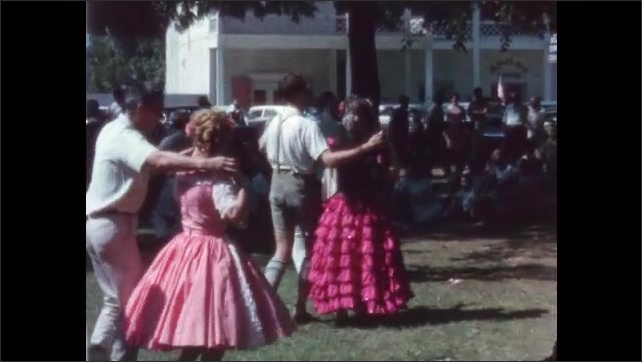 1960s: Men and women dance outside in a park.