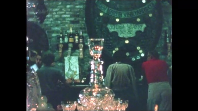 1960s: Man stands behind bar, holds bottle of wine, talks. Wine decanter set. People stand at bar, man fills glasses. Wine glasses in window display.