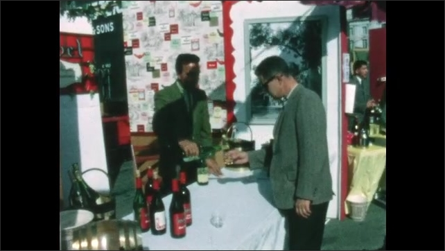 1960s: People stand outside, sip wine. Wine vendor pours man a sample of wine. People browse art prints at booth.