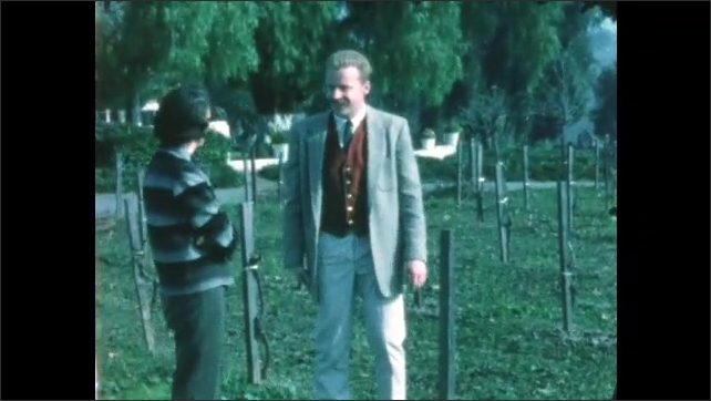 1960s: Vineyard posts. Man and woman stand next to vineyard posts. Empty vineyard.