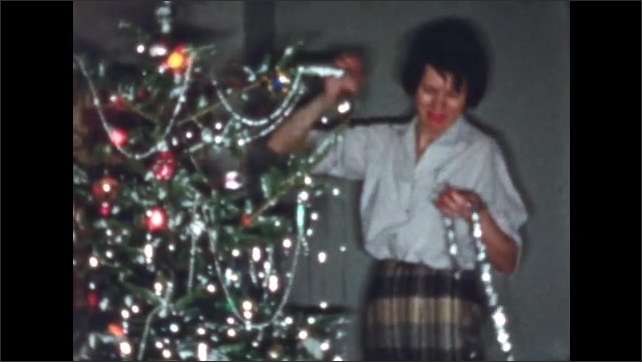1960s: UNITED STATES: lady drapes silver tinsel on branch of Christmas tree. Lady on steps.