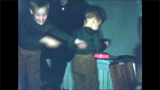 1960s: UNITED STATES: boys talk with man. Boys dance at home