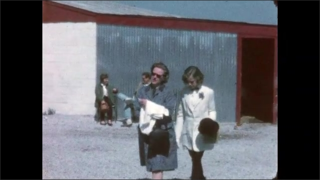 1960s:  UNITED STATES: girl and parents walk away from stables after show. Man looks at horse. Rider and horse.