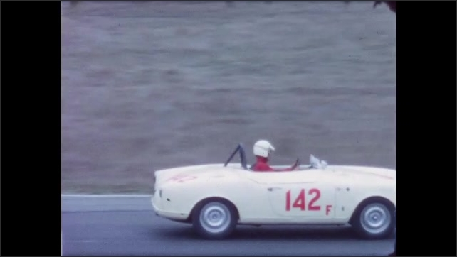 1960s: two racecars driving around a curve