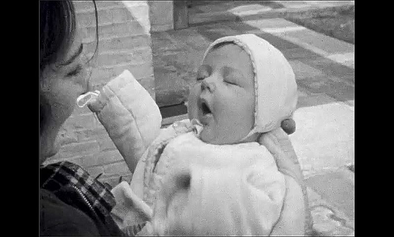 1930s: UNITED STATES: baby looks at camera. Baby smiles. Lady holds baby. Men by buildings. Geese in field.