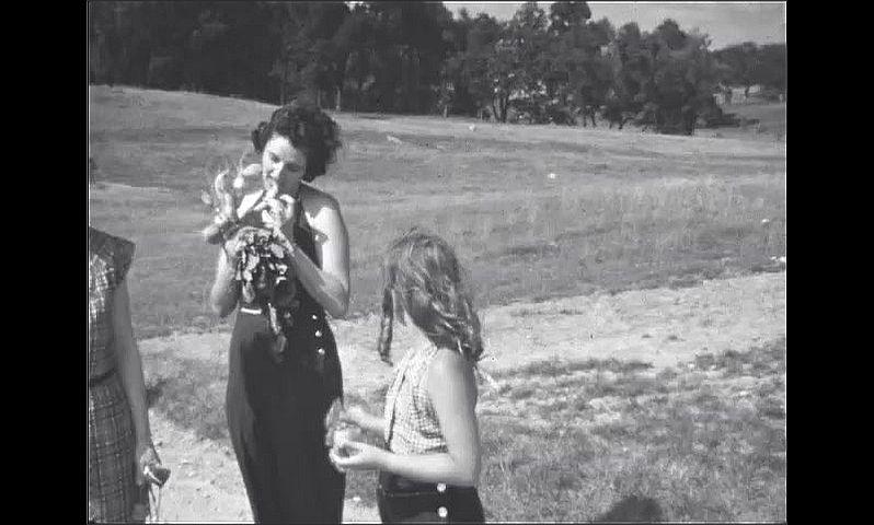 1930s: UNITED STATES: ladies walk along track. Man smiles at camera.