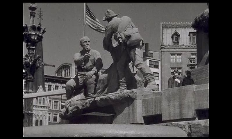 1940s: UNITED STATES: American flag behind statue. Men carved from stone.