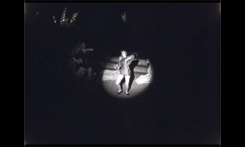 1940s: UNITED STATES: artist paints picture on stage. Man plays piano. Skeleton on stage.