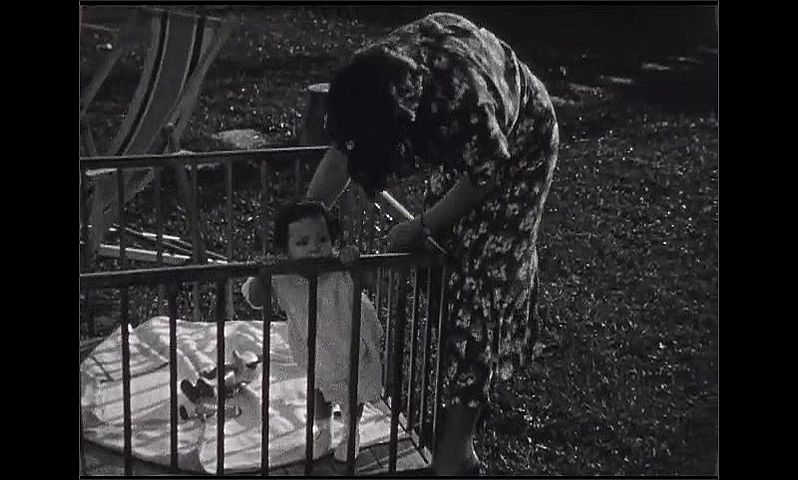 1930s: Baby girl holds onto edge of crib and chews on it as woman in floral dress fusses with her. Baby chewing on her crib, mother's hands anxiously fidgeting close by.