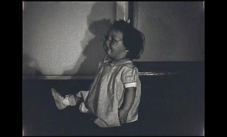 1930s: Baby girl with bow in hair crawls towards ball on floor, sits down, looks around and smiles. Baby girl looks at camera, opens her mouth and turns towards the wall.