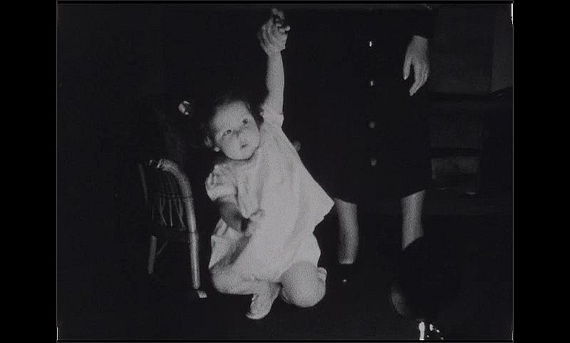 1930s: Baby girl crawls across floor, sits, crawls again. Woman holds baby's arm as she slowly sinks onto the floor, woman lets go, baby grabs rocking chair, then rubs her face.
