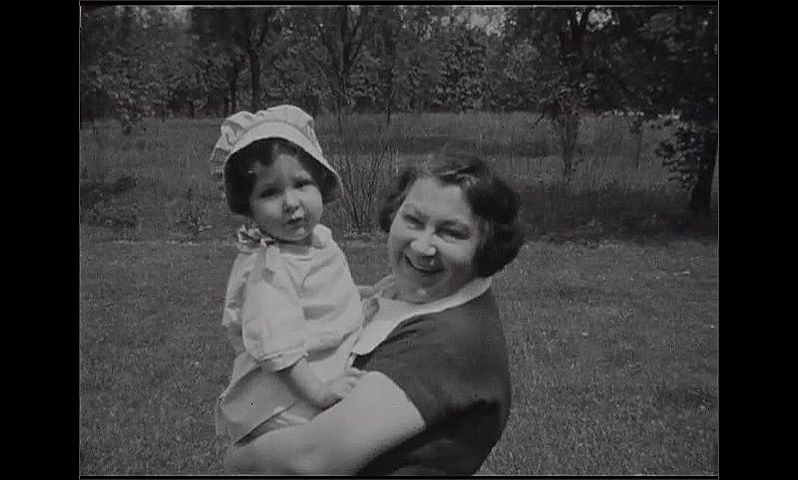 1930s: Baby girl in bonnet smiles at camera, puts thumb in mouth. Woman holds up baby and smiles. Woman shows baby a pot, but baby recoils backward, looks at camera.