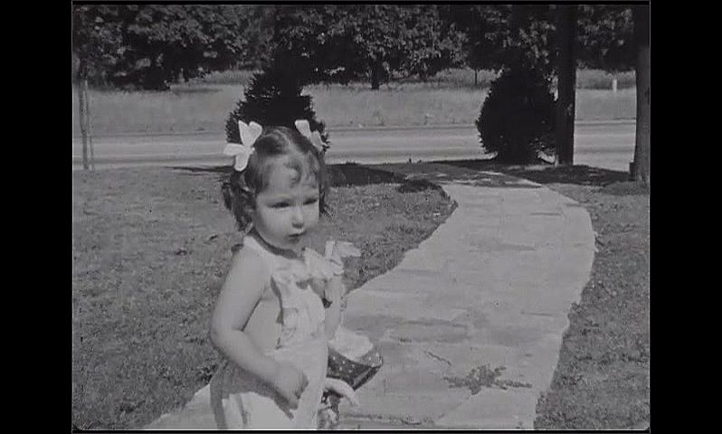1930s: Baby girl in romper and pigtails holds doll upside down by leg. She looks at the camera. She walks and trips on walkway. She watches her shadow on the stones.