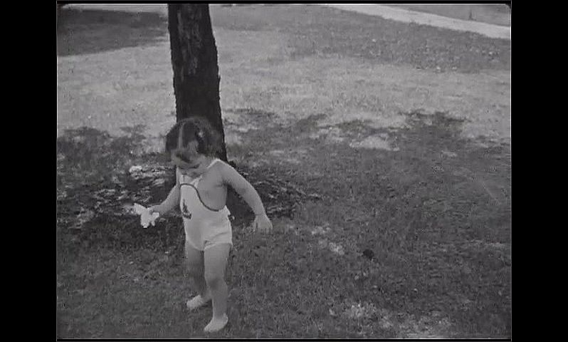 1930s: Baby girl in swimsuit stands by active sprinkler, woman beckons. Baby walks on grass by sprinkler. Baby puts hand to head, stares at camera. Baby stands in sprinkler, makes funny faces.