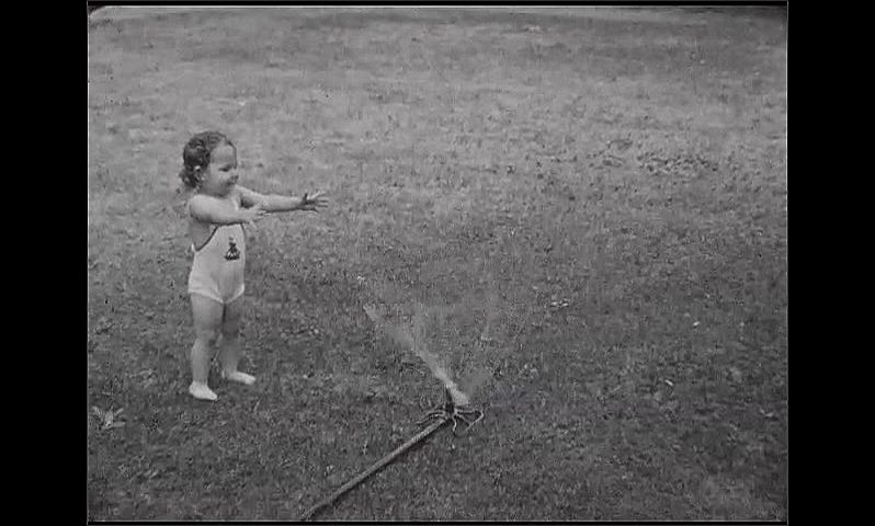 1930s: Baby girl stands in sprinkler, makes funny faces, woman runs by, scoops her up. Baby walks smiling. Baby stands by sprinkler, hands outstretched. Woman walks down path, other stands, looks.