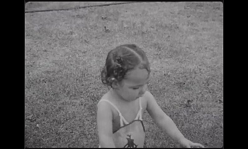 1930s: Baby girl holds out hands to spinning sprinkler, bounces arms. Wet baby looks at camera. She puts her hands to her mouth to drink the water.