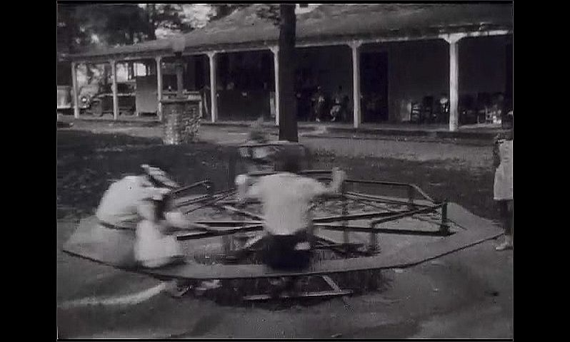 1930s: Woman holds toddler baby girl on roundabout at playground with two another boy and girl as it spins round. Baby girl stands in playground, one finger in her mouth and a ribbon in her hair.
