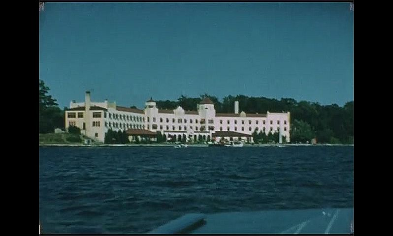 1940s: People stand on dock near boat. Women walk down dock. Large hotel on lakefront. Flag on boat.