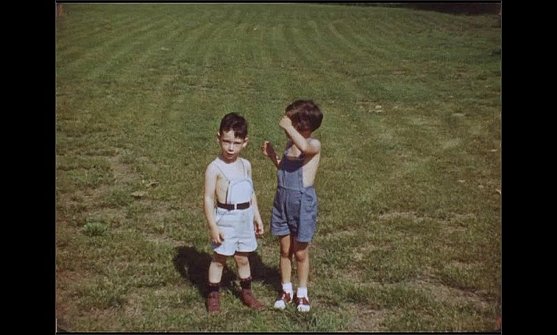 1940s: People walk near large building. Children stand in grass, run across grassy field towards building.