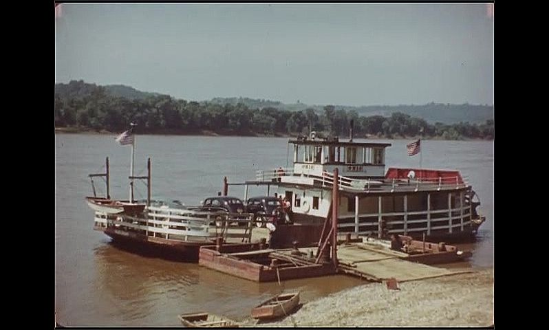 1940s: People stand on dock next to car. Ferry pulls up to dock. Women and children pose by boat railing. People stand on shore, watch boat pull away from dock.