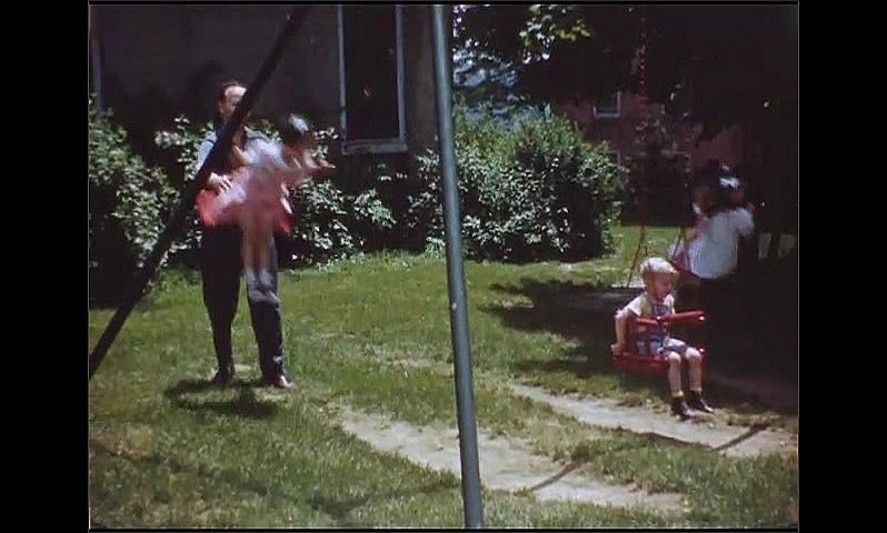 1940s: Children swing on swings. Woman pushes boy around on merry go round. Man pushes girl on swing. People walk across playground. People walk down path through woods.