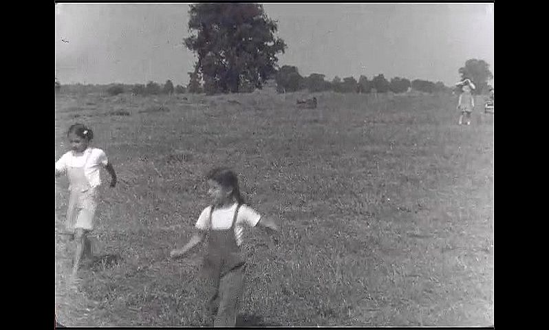 1940s: Children stand together in field. Children run across field. Men move bales of hay. Woman stands in field with children, men ride away on back of tractor.