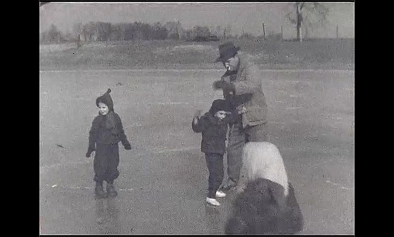 1940s: Man and children ice skate on frozen pond. Man holds child's hands. Men play hockey on ice.