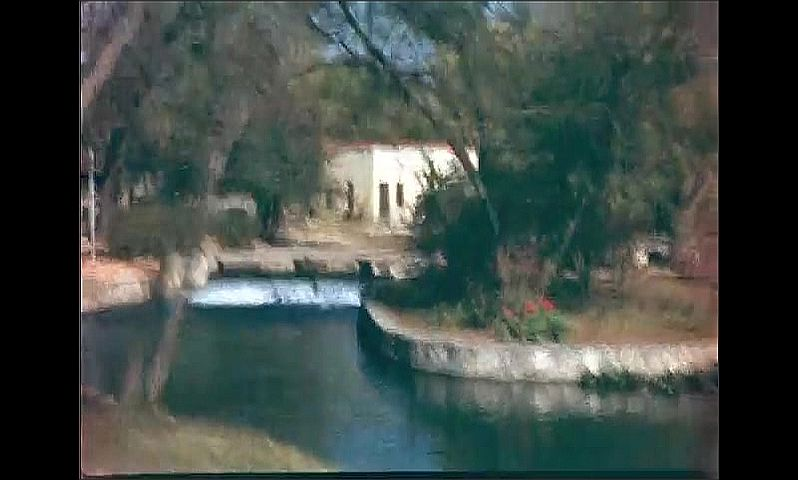 1930s: Car drives past rock buildings and towers. Car drives past homes and lakes. Car drives past river and dam.