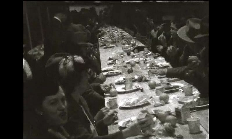 1940s: Dozens of men and women seated at very long dining table, women talk and laugh, man stands over. Lady and man stand by wall, smile. Band plays with guitars, violin and accordion.