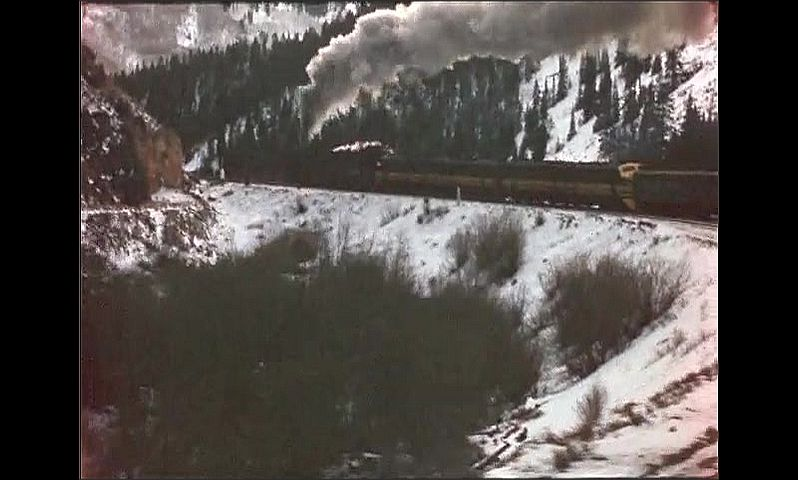 1940s: A bridge and buildings in a snowy, mountainous landscape. Snowy hillsides with barren trees and a rock formation. Train rolls down snowy tracks. Rear of train rounds a bend.
