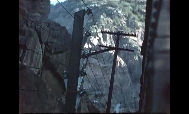 1940s: Train waits on tracks next to rocky river in between two mountains. Telephone poles and rocks from moving train window. Mountains at side of railroad tracks.