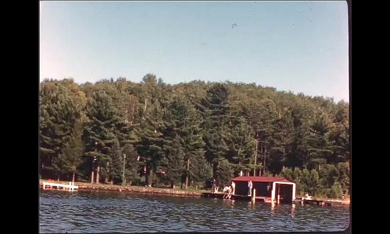 1940s: Man and women sit on boat, turn around and wave. Boat travels past lake houses and docks.