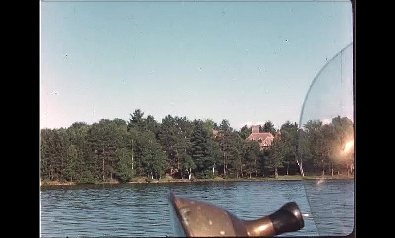1940s: Lake houses. Lake and trees. Boat speeds across water.