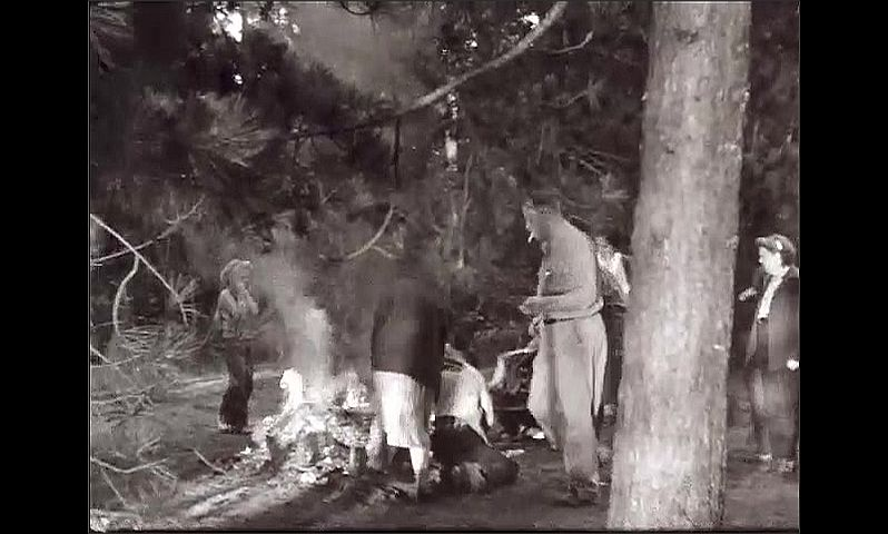 1940s: People gather outside at long table to eat. People roast food in large fire.