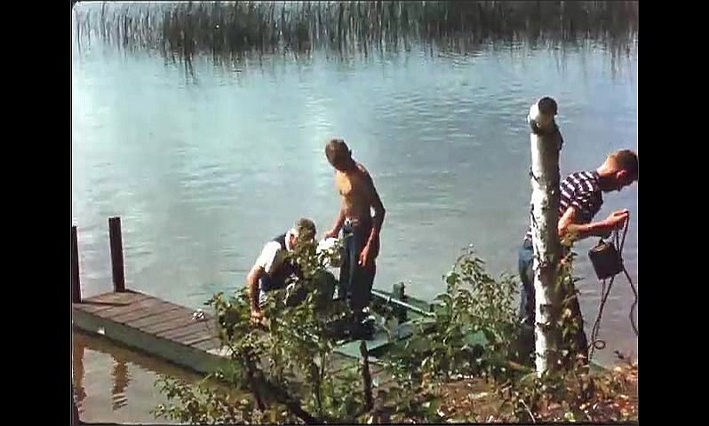 1940s: People row boat up to small dock. Boys step out of boat, boy holds fish on line.