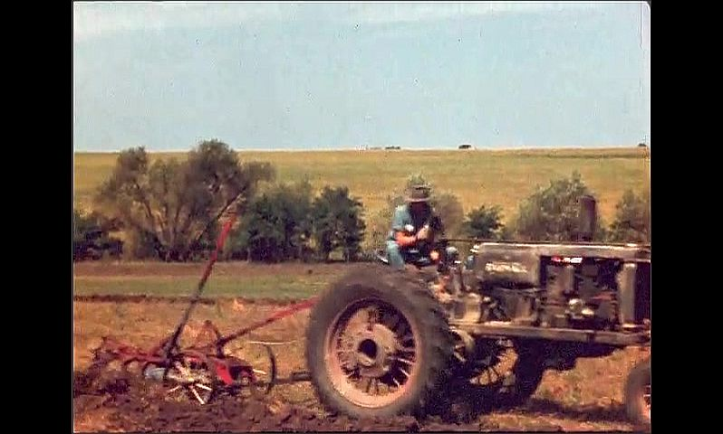 1940s: Man drives tractor through field, tills field. People watch tractor go by.