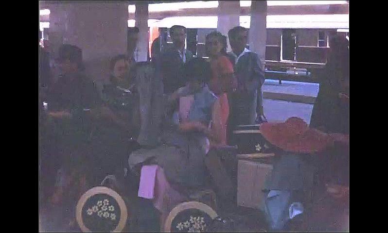 1940s: Women seated at platform at train station.
