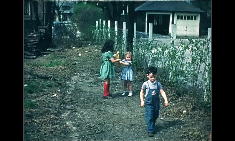 1940s: Close up of woman. Long shot, kids in yard with man. Kids standing in yard. Girls standing, girl holds toy.