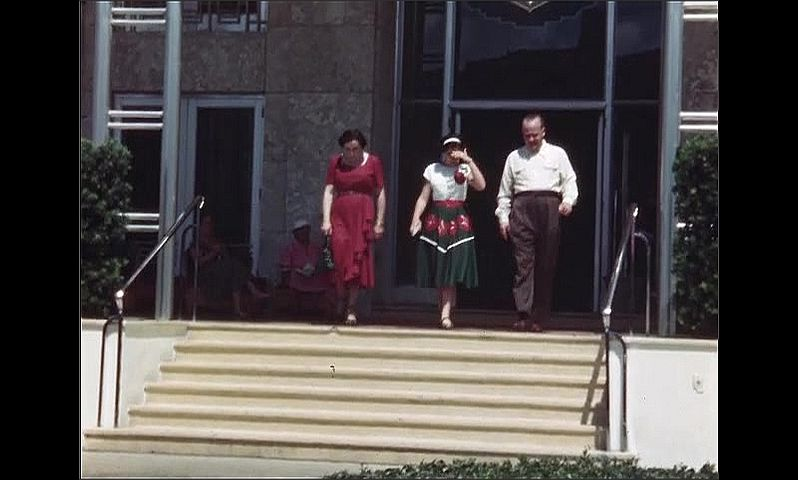 1940s: Long shot, man and woman pose on steps to building. Man, woman and girl walk down steps. Man and woman walking with girl.