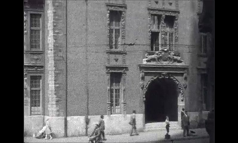 1920s: GERMANY: EUROPE: man on bike in street. Buildings in city. Man with parcel under arm.