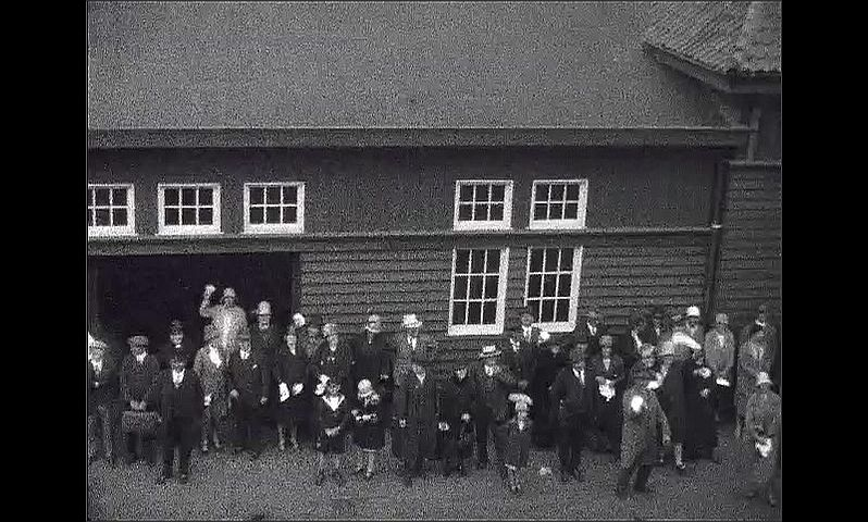 1920s: GERMANY: EUROPE: dock buildings by coast. People outside wooden building on coast. People wave at camera.