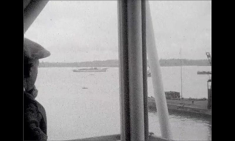1920s: UNITED STATES: funnels on ship. Life boats on ship. View across dock from ship. Men walk on deck.