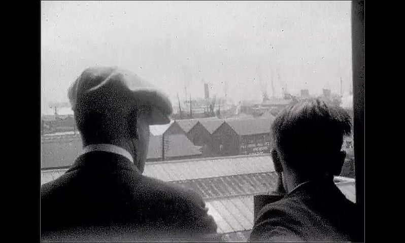 1920s: UNITED STATES: men in suits and caps on deck of ship. Men look out at view. Man waves cap at dock. View of dock and buildings