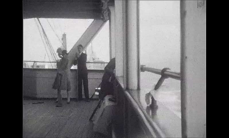 1920s: UNITED STATES: passengers play shove the puck on deck. Lady with dog on deck of ship. Chalk games on deck of ship