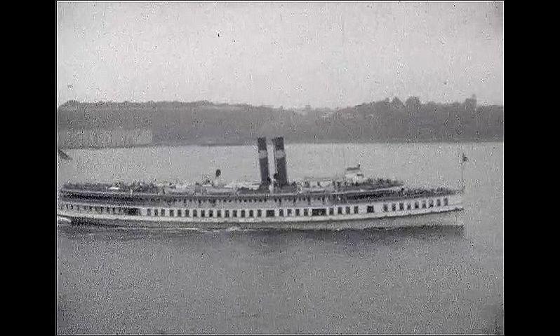 1920s: UNITED STATES: men walk along deck of ship. Passing ships at sea.