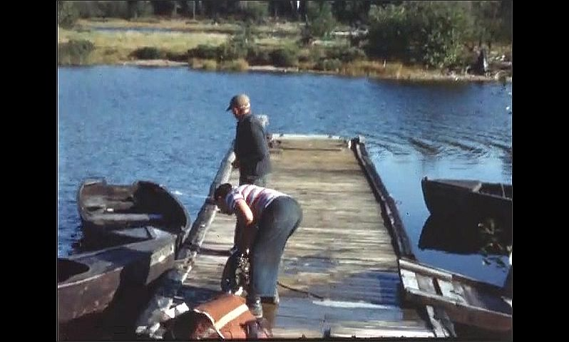 1940s: Man stands on dock over water as other man climbs into row boat. Two men stand on dock, one holds boat motor then sets it down. Man on dock hands rope to man in boat in water.