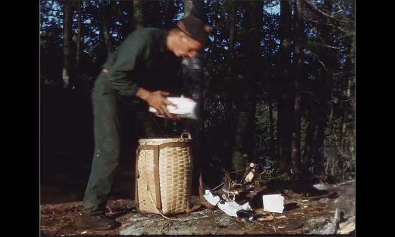 1940s: Campsite with boiling pot over campfire. Man removes supplies from basket.
