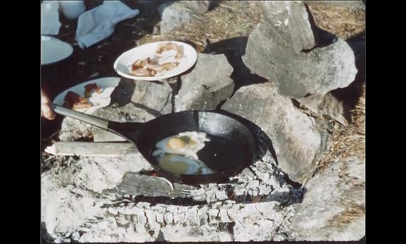 1940s: Man breaks eggs into frying pan at campsite. Frying pan with eggs cook over campfire. Man spreads butter on bread.
