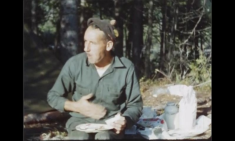 1940s: Man at campsite sits while eating breakfast.